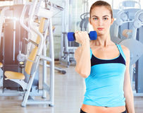 Sporty female doing physical exercise in gym Royalty Free Stock Photos