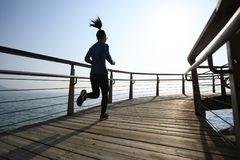 Sporty female jogger morning exercise on seaside boardwalk Royalty Free Stock Photo