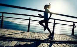 Sporty female jogger morning exercise on seaside boardwalk Stock Photography