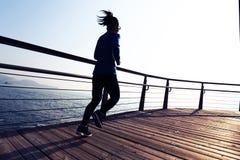 Female jogger morning exercise on seaside boardwalk during sunrise Royalty Free Stock Image