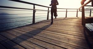 Female jogger morning exercise on seaside boardwalk during sunrise. Sporty female jogger morning exercise on seaside boardwalk during sunrise Royalty Free Stock Image