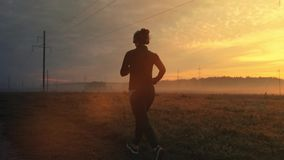 Sporty female jogger is running and training outside at the nature. Athletic woman is running during sunset time