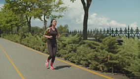 Sporty female jogging along running path in park stock video