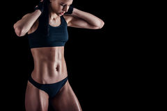 Sporty female with perfect body against black background. Fitness woman in sportswear with ideal fitness body. Royalty Free Stock Photo