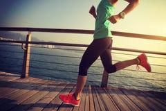 Runner running on seaside boardwalk during sunrise. Sporty female runner running on seaside boardwalk during sunrise Stock Image