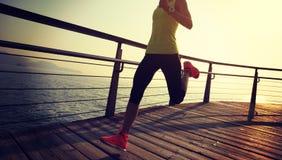 Runner running on seaside boardwalk during sunrise. Sporty female runner running on seaside boardwalk during sunrise Stock Photo