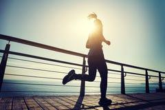 Runner running on seaside boardwalk during sunrise. Sporty female runner running on seaside boardwalk during sunrise Royalty Free Stock Image