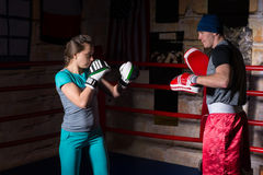 Sporty female in sportswear and in boxing gloves training with h stock images