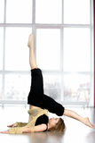 Sporty female standing in yoga Shoulderstand pose in class Royalty Free Stock Images