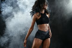Sporty fit black skin woman, athlete makes fitness exercising on dark background. royalty free stock images