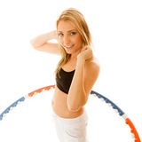 Sporty fit girl doing exercise with hula hoop. Royalty Free Stock Photos