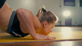 Fit Sporty Lady is Doing Stretching Exercises during Workout in the Training Gym. Sporty Fit Girl is Doing Stretching Cat Exercises during Workout in the stock footage