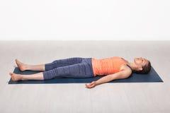 Sporty fit girl relaxes in yoga asana Savasana Royalty Free Stock Photo