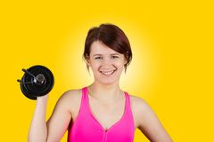 Sporty fit healthy smiling beautiful woman, red head girl holding a dumbbell royalty free stock image