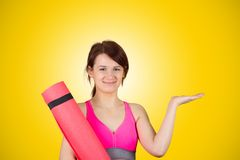 Sporty fit healthy smiling beautiful woman, red head girl holds an yoga mat royalty free stock image