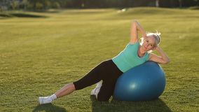 Sporty fit lady doing side crunches on ball stock footage