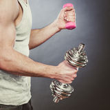 Sporty fit man lifting light and heavy dumbbells. Stock Images