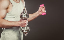 Sporty fit man lifting light and heavy dumbbells. Stock Image