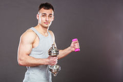 Sporty fit man lifting light and heavy dumbbells. Royalty Free Stock Image