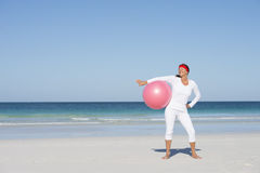 Sporty fit mature woman exercising beach Royalty Free Stock Photos