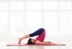 Sporty fit mature yogini practices yoga halasana or plow pose stock photo