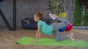 Sporty fit preadolescent girl performing donkey kick exercise