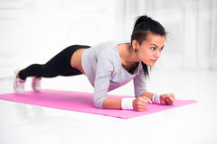 Sporty fit sliming girl doing plank exercise in. Yoga class. fitness, home and diet concept stock photos