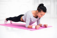 Sporty fit sliming girl doing plank exercise in yoga class. fitness, home and diet concept. Stock Photo