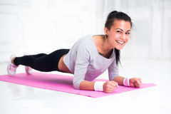 Sporty fit sliming girl doing plank exercise in. Yoga class looking at camera. fitness, home and diet concept stock images