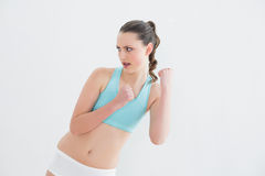 Sporty fit woman clenching fists against wall Royalty Free Stock Photography