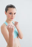 Sporty fit woman clenching fists against wall Royalty Free Stock Images