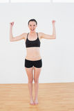 Sporty fit woman clenching fists in fitness studio Stock Photography