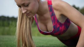 Sporty fit woman exercising by doing push-ups stock video footage