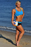 A sporty fit woman in her fitness clothes holding a volleyball ball Stock Photography