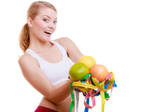 Sporty fit woman with measure tapes fruits. Time for diet slimming. Royalty Free Stock Photography