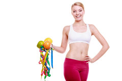 Sporty fit woman with measure tapes fruits. Time for diet slimming. Royalty Free Stock Photo