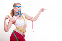 Sporty fit woman with measure tapes. Time for diet slimming. Royalty Free Stock Image