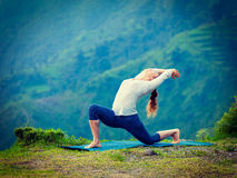 Sporty fit woman practices yoga asana Anjaneyasana in mountains Royalty Free Stock Images