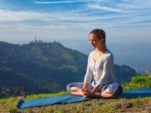 Sporty fit woman practices yoga asana Baddha Konasana outdoors Royalty Free Stock Images