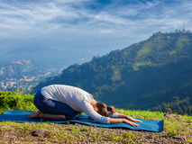 Sporty fit woman practices yoga asana Balasana Royalty Free Stock Images
