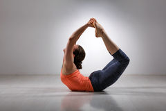 Sporty fit woman practices yoga asana Dhanurasana Stock Images
