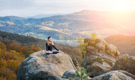 Sporty fit woman is practicing yoga on the top of the mountain Stock Images