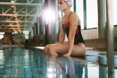 Sporty fit woman relaxing at swimming pool edge stock photos