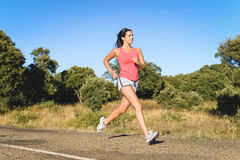 Sporty fit woman running in country road Royalty Free Stock Images