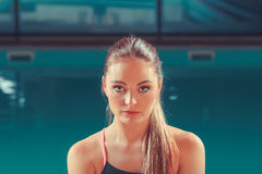 Sporty fit woman at swimming pool edge poolside. Stock Images