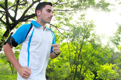 Sporty fit young man jogging while listening music. Portrait of sporty fit young man jogging while listening music on smarthphone Royalty Free Stock Image