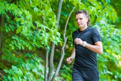 Sporty fit young man jogging while listening music Royalty Free Stock Photos