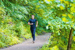 Sporty fit young man jogging while listening music. On smarthphone outdoor in park Stock Image