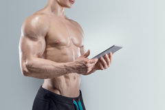 Sporty and fit young man using a digital tablet Stock Images