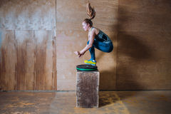 Sporty fit yuong woman jumping over high box during fitness workout, Side view. royalty free stock photography